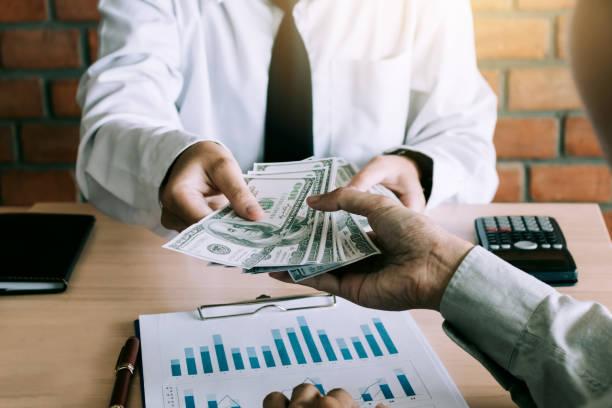 Businessman give dollar bills to partner.
